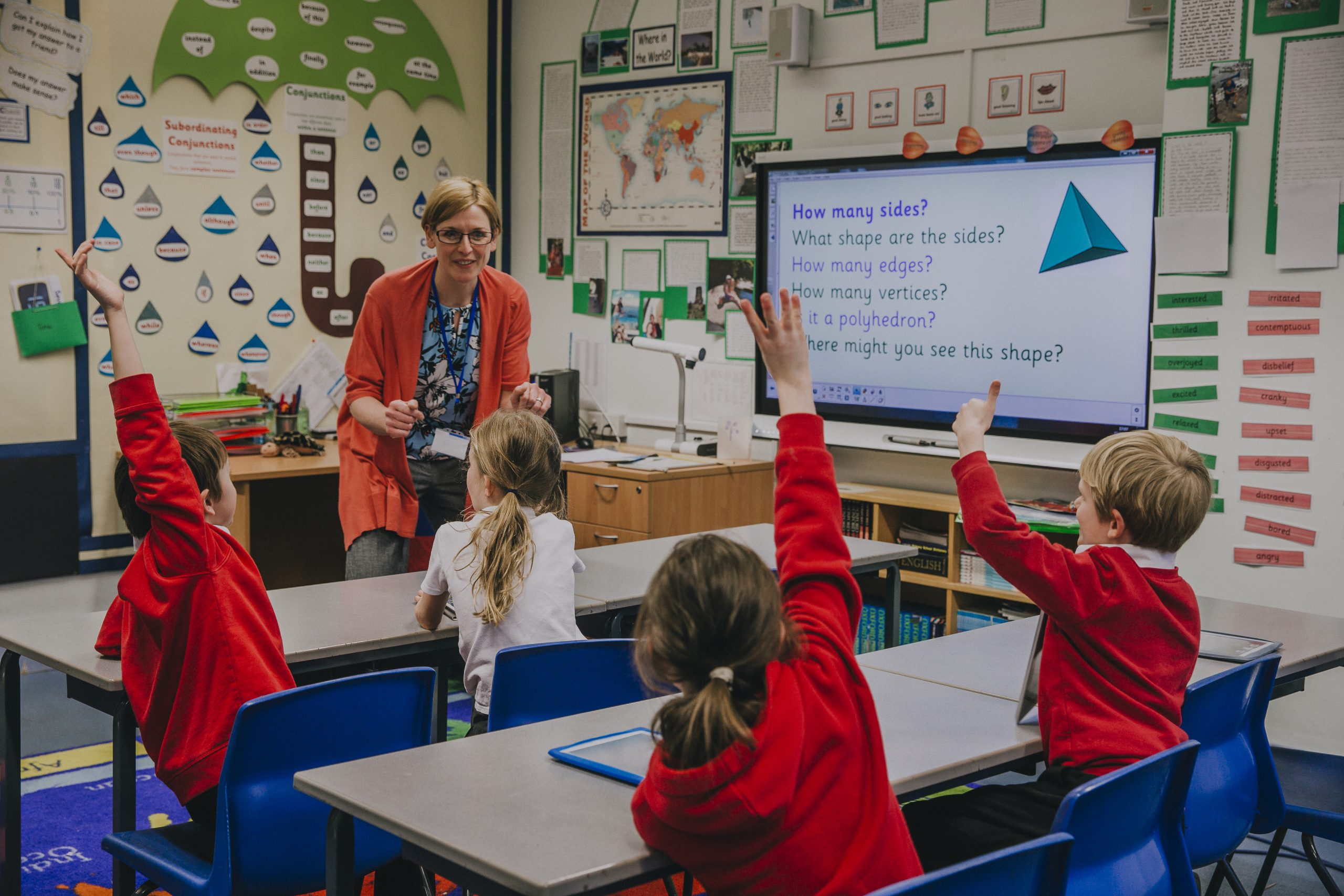 Female teacher is teaching shapes to her primary school students. She is asking hem a question and some of the students have their hand in the air to answer.