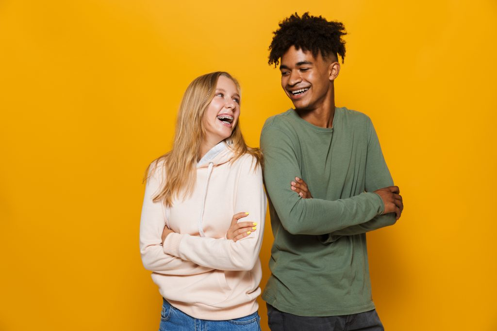 Photo of teenage people man and woman 16-18 with dental braces smiling isolated over yellow background