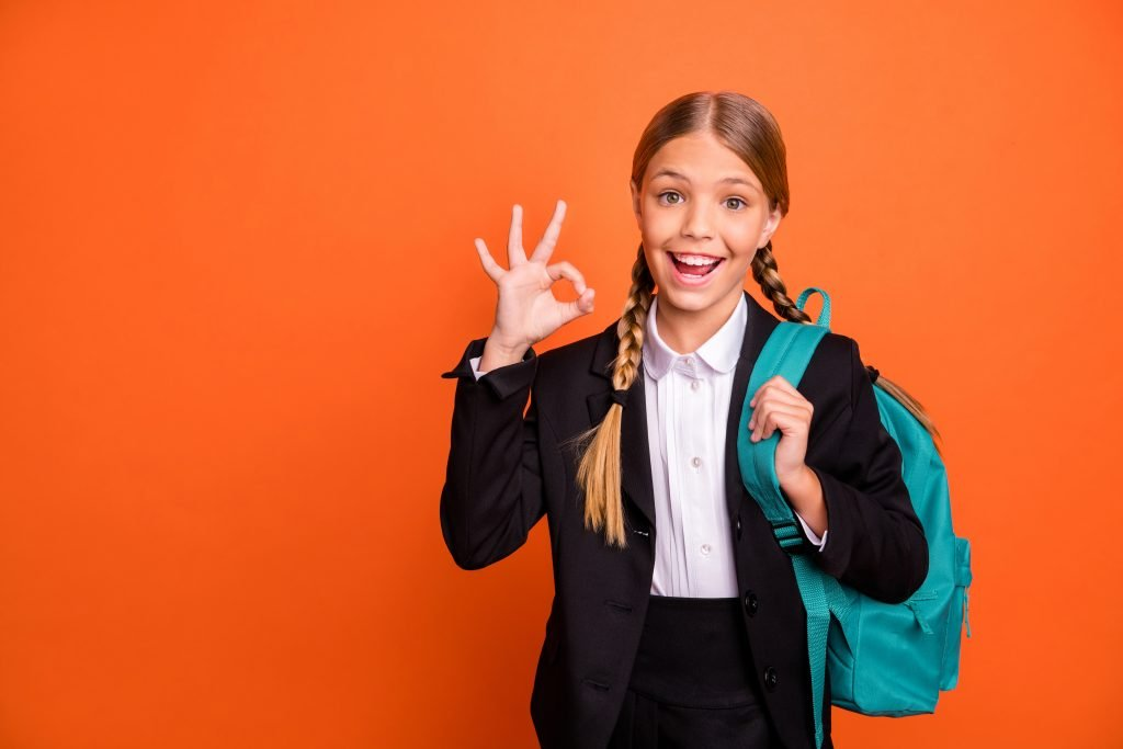 Close up photo beautiful she her little lady funny hairdo hand arm fingers, raised okey symbol approval quality news wear formalwear shirt blazer skirt school form bag isolated bright orange background