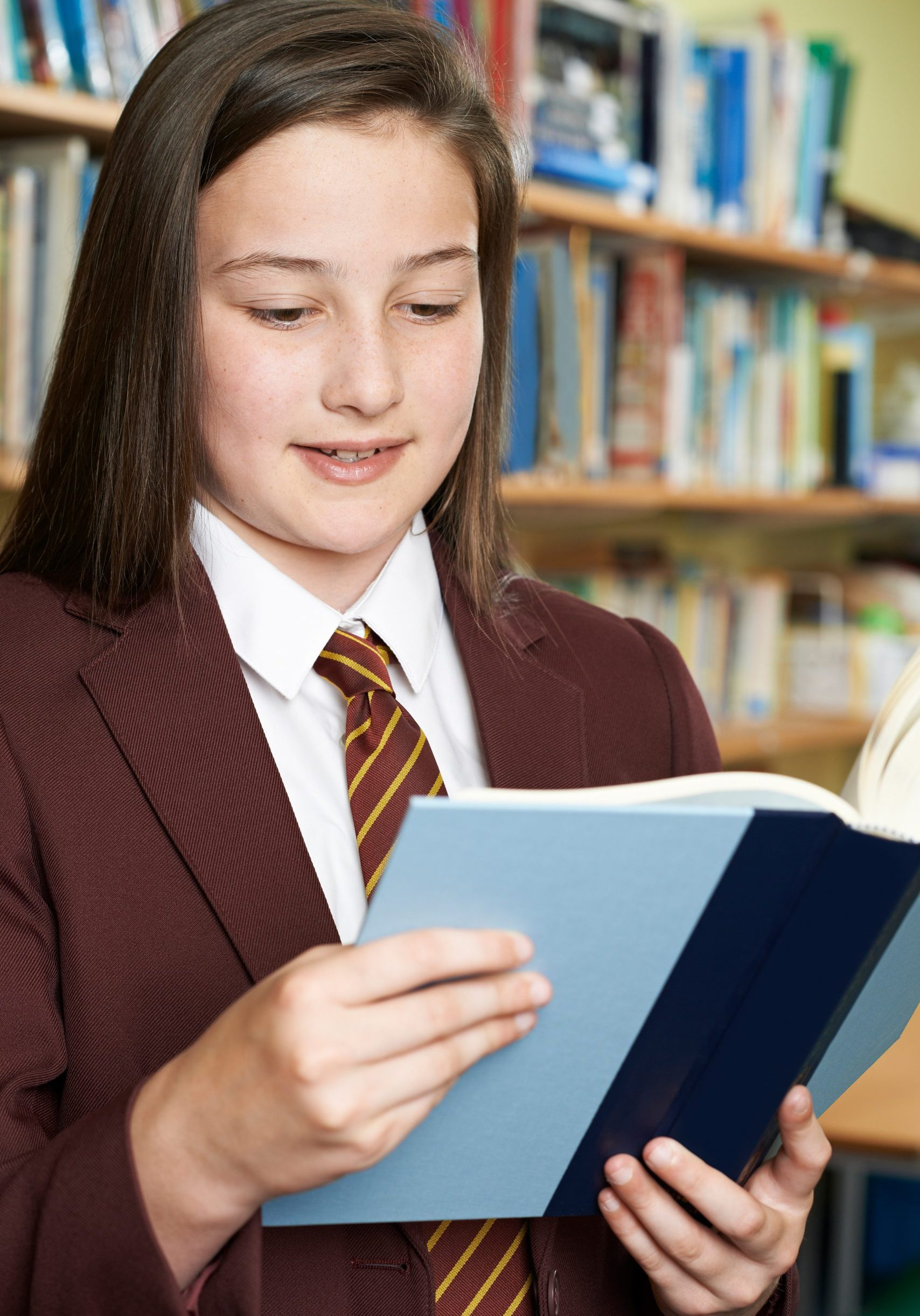 Girl Wearing School Uniform Reading Book In Library